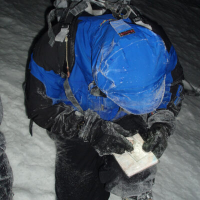 Person kneeling down, using a compass to orienteer in the snow.